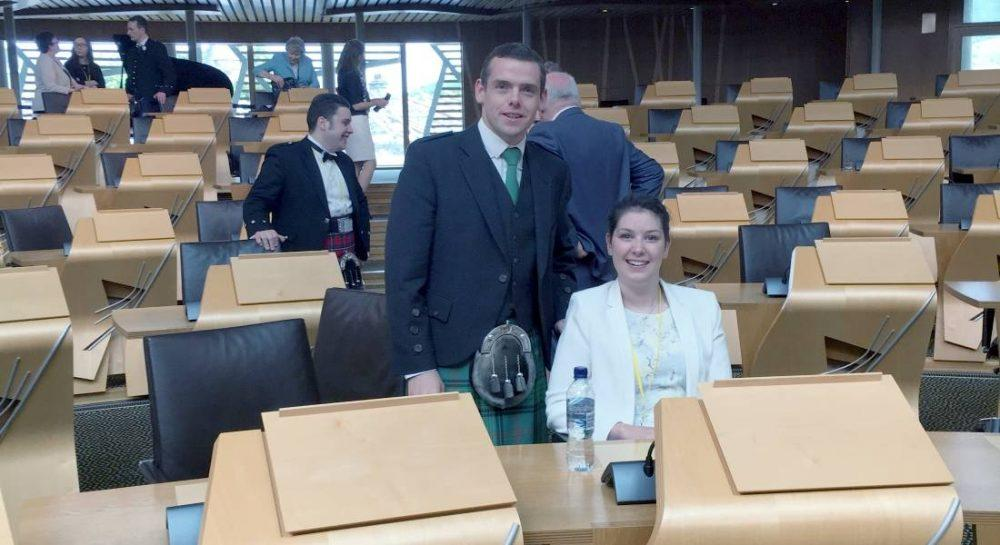 Lucy takes a seat in the chamber of the Scottish Parliament.