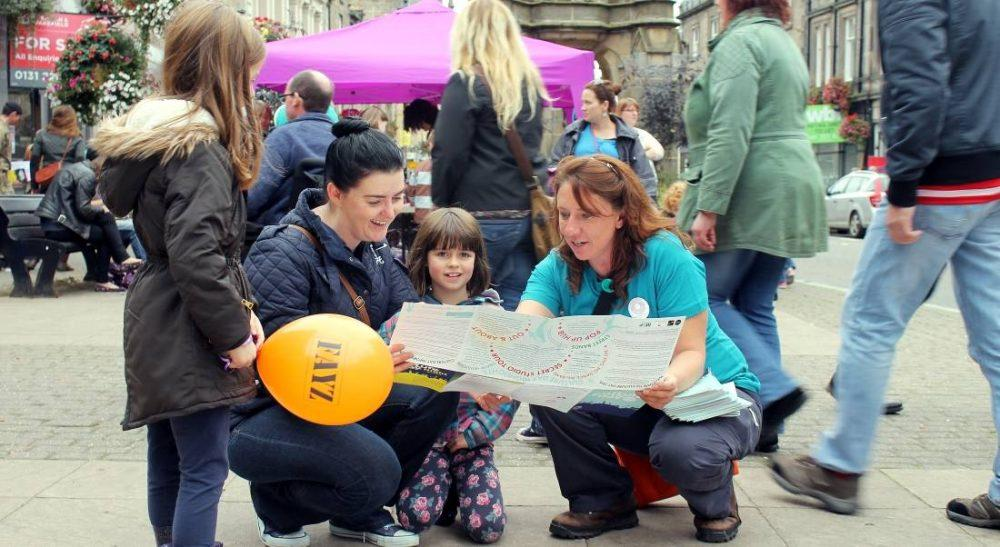 Festival visitors seeking out help from a Festival volunteer last year (pic: John Cudworth)